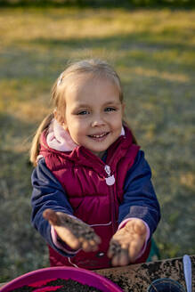 Portrait of smiling girl showing her dirty hands from gardening - ZEDF03334
