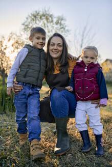 Portrait of happy mother with two kids in garden - ZEDF03340