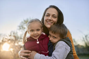 Portrait of happy mother hugging two kids outdoors - ZEDF03343