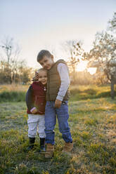 Affectionate brother and sister standing on a meadow at sunset - ZEDF03346