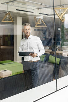 Mature businessman in office lounge looking out of window - PESF01946