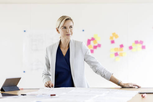 Blond businesswoman in conference room with adhesive notes at whiteboard - PESF01964