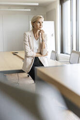 Blond businesswoman in conference room thinking - PESF01997