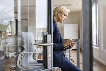 Blond businesswoman using tablet in conference room - PESF02012