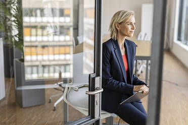 Blond businesswoman holding tablet in conference room - PESF02015
