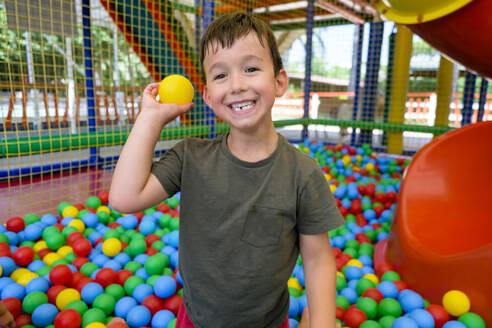 Smiling boy throwing ball in ball pit - MGIF00911