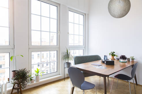 Dining table in bright living room with large windows - FKF03721