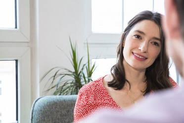 Smiling woman looking at man at home - FKF03739