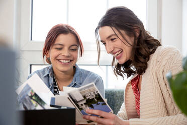 Happy mother and daughter at home looking at photographs - FKF03748