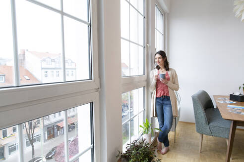 Woman standing at the window at home looking out - FKF03757