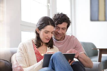 Couple sitting on couch at home using tablet - FKF03766