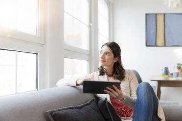 Woman sitting on couch at home using tablet - FKF03769