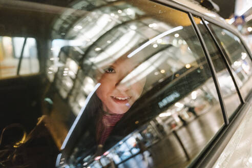 Young woman inside a taxi in the city at night - AHSF02378