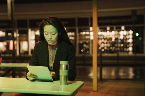 Young woman using tablet on a coffee shop terrace in the city at night, Frankfurt, Germany - AHSF02384