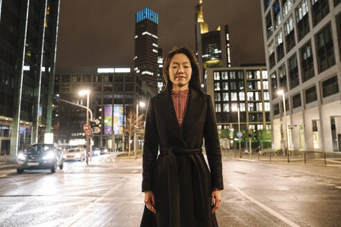 Portrait of young woman with eyes closed in the city at night, Frankfurt, Germany - AHSF02405