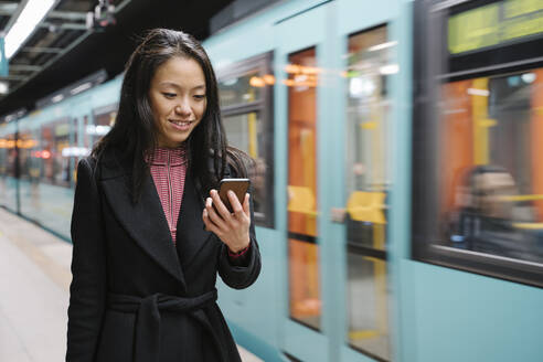 Young woman using smartphone in metro station - AHSF02423