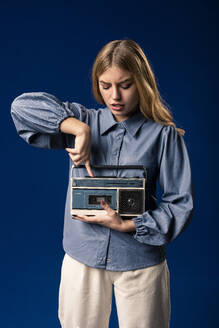 Blond woman with cassette player in front of blue background - AGGF00059