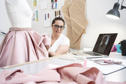 Seamstress working in tailor shop and presenting skirt via video call - VPIF02362