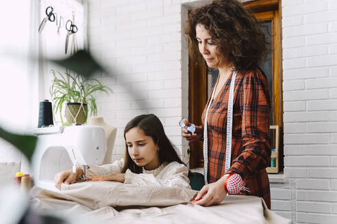 Mother and daughter sewing at home - ERRF03566