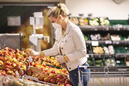 Teenage girl wearing protectice mask and gloves choosing apples at supermarket - ASCF01256