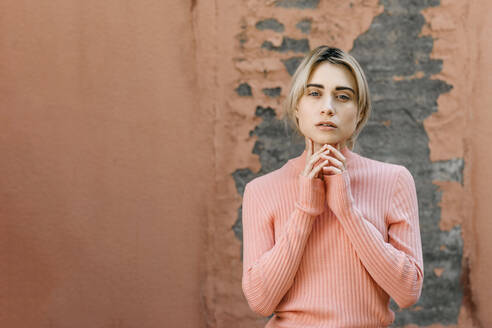Portrait of blond woman wearing pink turtleneck pullover in front of a pink wall - TCEF00534