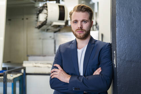 Portrait of a confident young businessman in a factory - DIGF10056