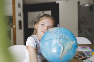 Portrait of confident girl with globe at home looking at distance - HMEF00918