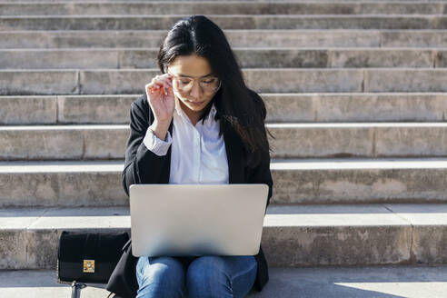 Young businesswoman sitting on stairs outdoors using laptop - XLGF00108