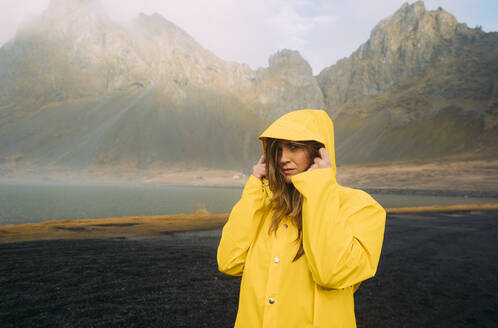 Portrait of woman wearing yellow coat standing at beach in Hvalnes Nature Reserve Beach, Iceland - DAMF00423