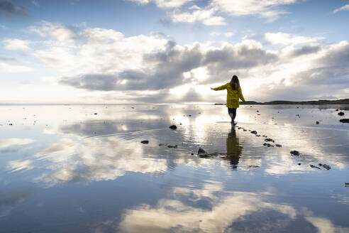 Woman walking amidst sea with reflection in Hvalnes Nature Reserve Beach, Iceland - DAMF00426
