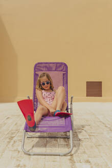 Portrait of girl wearing sunglasses, swimsuit and diving flippers sitting on beach lounger on roof terrace - ERRF03610