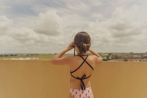 Back view of girl in swimsuit standing on roof terrace looking through binoculars - ERRF03628