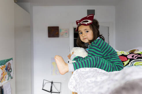 Portrait of little girl with fox mask sitting on barefoot bunk bed at home - VABF02844