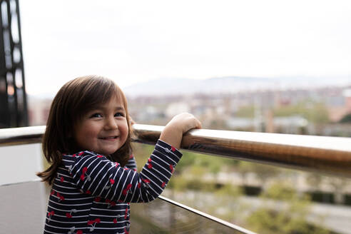 Portrait of happy little girl on balcony - VABF02871