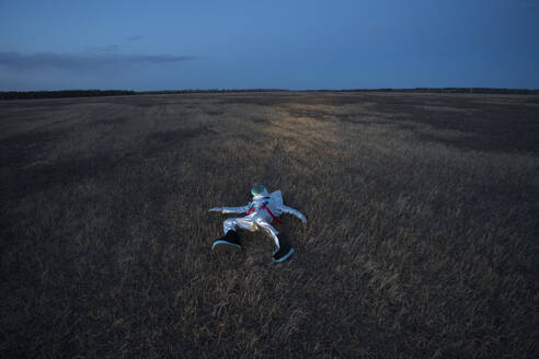 Spacewoman lying on meadow in the evening - VPIF02388