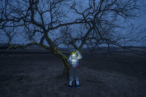 Spacewoman discovering a tree in the evening - VPIF02394
