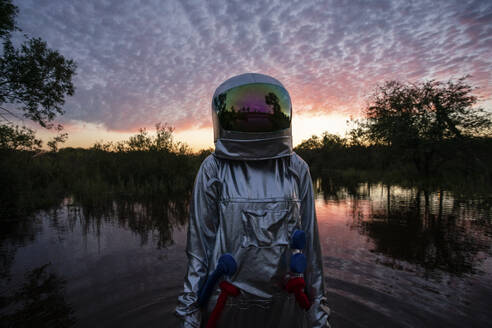 Portrait of spacewoman standing in water at sunset - VPIF02403