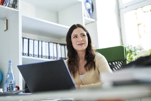 Beautiful businesswoman looking away while using laptop in office - MMIF00204