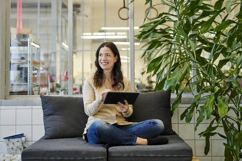 Smiling businesswoman using digital tablet while sitting on sofa at office - MMIF00213