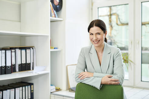 Portrait of smiling businesswoman with arms crossed on chair at office - MMIF00231