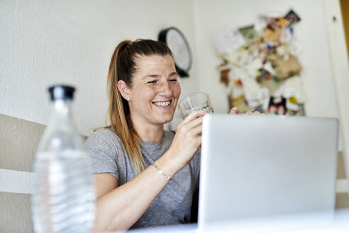 Smiling woman drinking water while using laptop in living room - MMIF00237