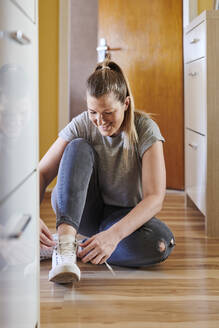 Smiling woman tying shoelace while sitting on hardwood floor at home - MMIF00249