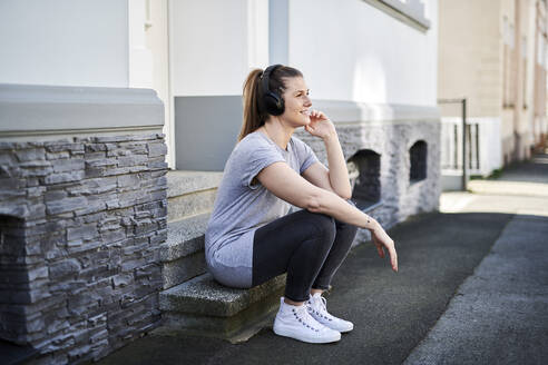 Woman listening music on wireless headphones while sitting on steps - MMIF00252