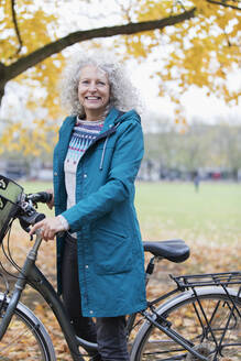 Portrait smiling, confident senior woman bike riding in autumn park - CAIF26398