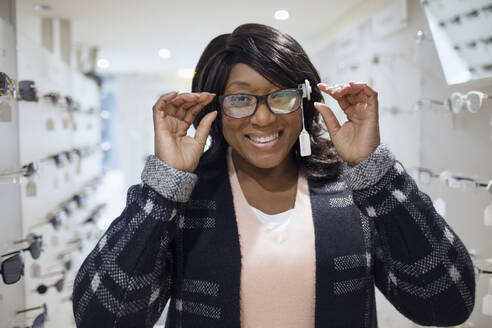 Portrait confident woman shopping for eyeglasses in optometry shop - CAIF26428