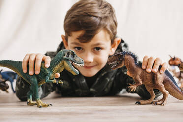 Smiling little boy lying on the floor playing with toy dinosaurs - JRFF04405