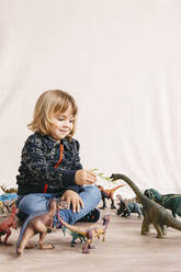 Portrait of cute little girl sitting on the floor feeding toy dinosaur - JRFF04411