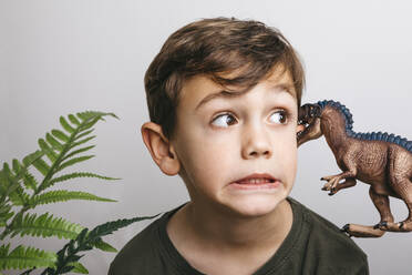 Portrait of little boy with toy dinosaur pulling funny face - JRFF04414