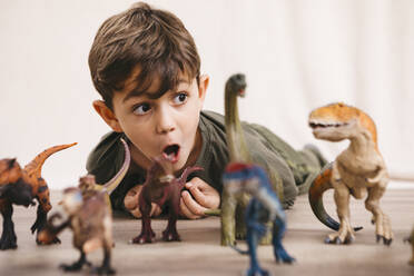 Portrait of little boy playing with toy dinosaurs - JRFF04417