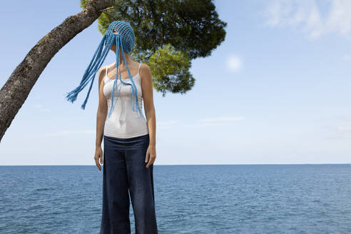 Woman wearing crocheted blue headdress with fringes standing in front of the sea - PSTF00684
